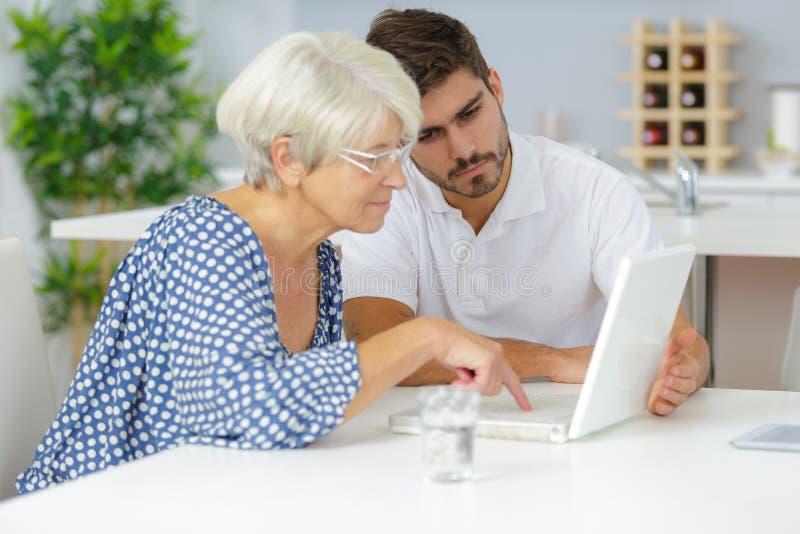 Młody człowiek pomaga starszej damy używać laptop zdjęcia royalty free