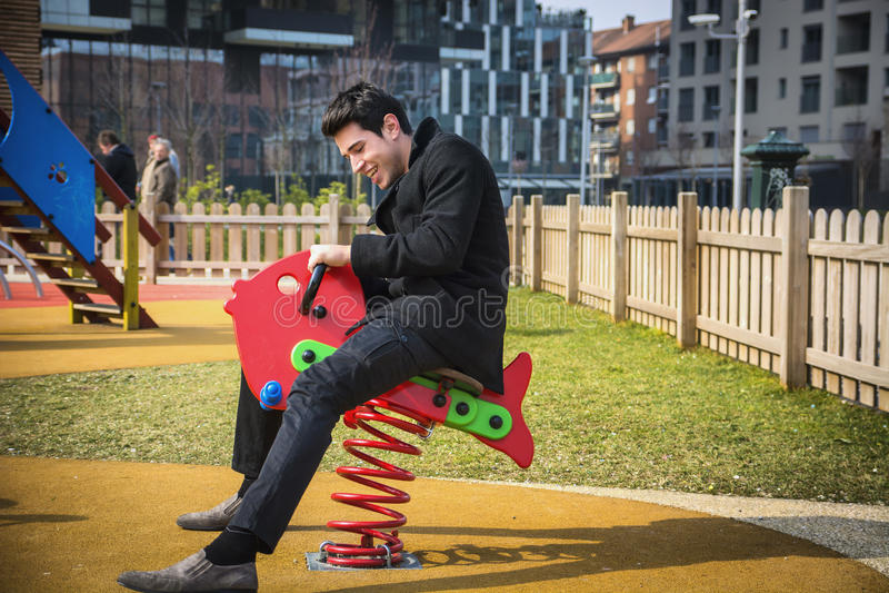 Młody człowiek ponownie przeżyć jego dzieciństwa kursowanie w children boisku zdjęcia stock