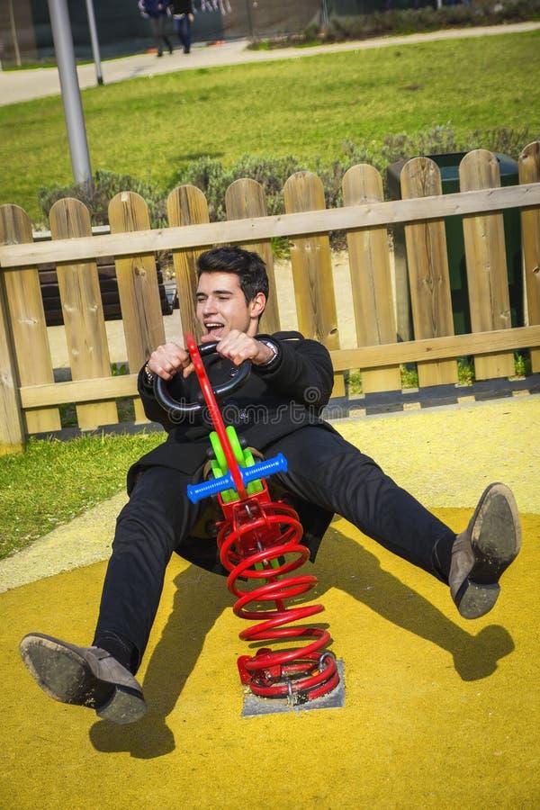 Młody człowiek ponownie przeżyć jego dzieciństwa kursowanie w children boisku zdjęcie stock