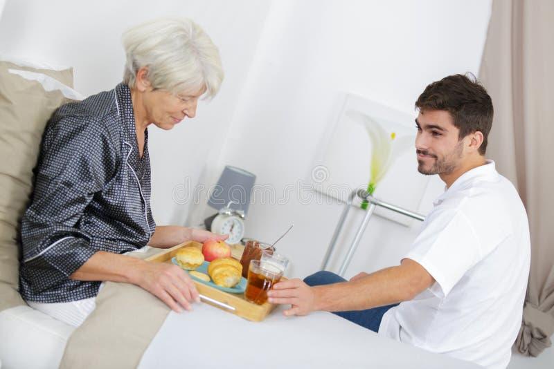 Młody człowiek porci śniadanie w łóżku starsza dama zdjęcia royalty free