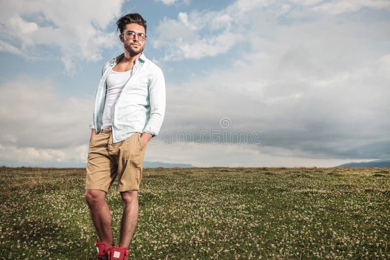Młody człowiek pozuje w polu kwiaty pełno zdjęcia stock
