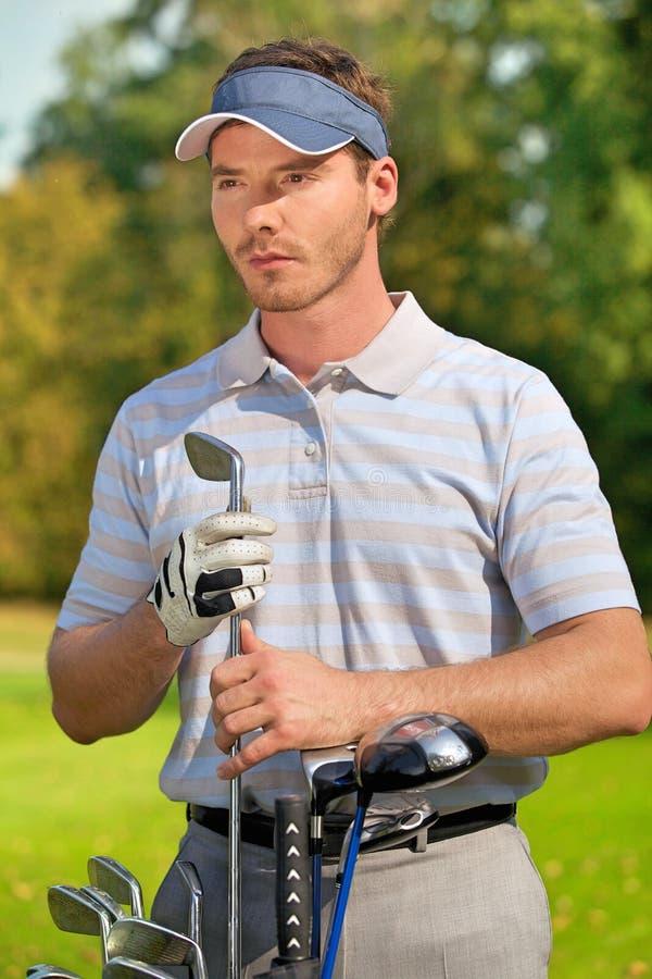 Młody człowiek pozycja golfową torbą kije pełno zdjęcia royalty free