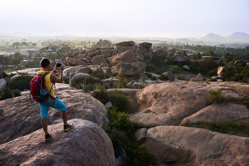 Młody człowiek pozycja na robić fotografii dolina i górze zdjęcie stock
