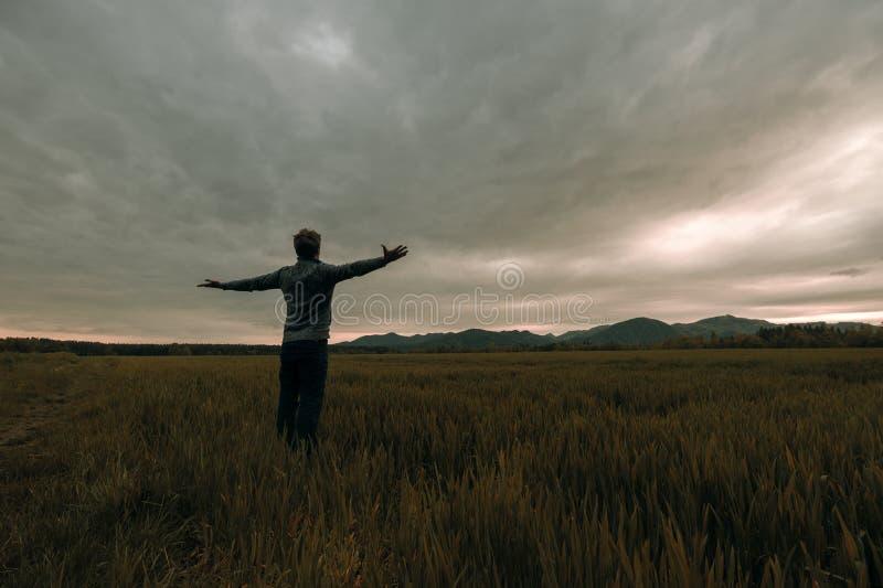 Młody człowiek pozycja w łące pod grzmotu niebem zdjęcie royalty free
