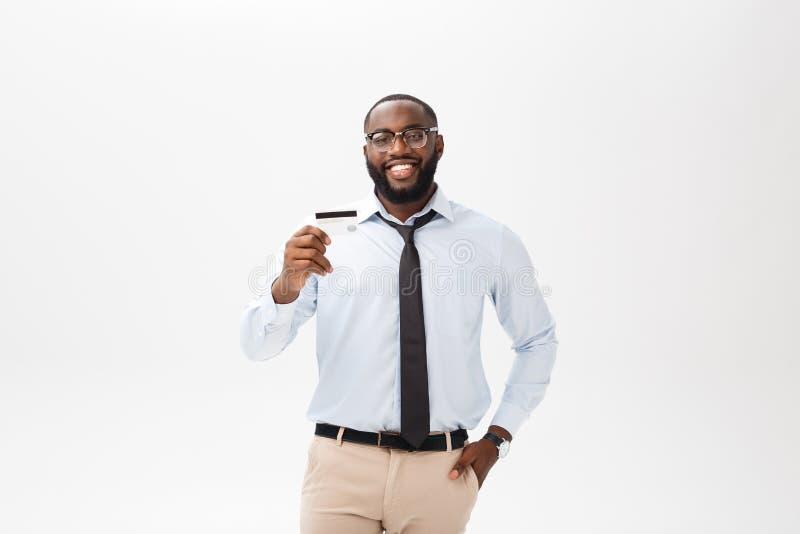 Młody człowiek pozycja w koszula pokazuje kartę kredytową, spojrzenia przy kamery ono uśmiecha się obrazy stock