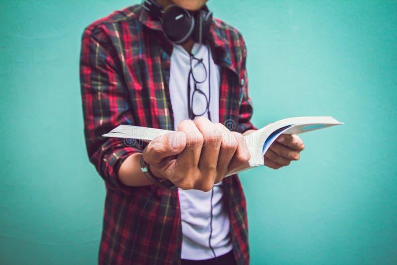 Młody człowiek pozycja w Szkockiej koszulowej czytelniczej książce na zieleni zdjęcie royalty free