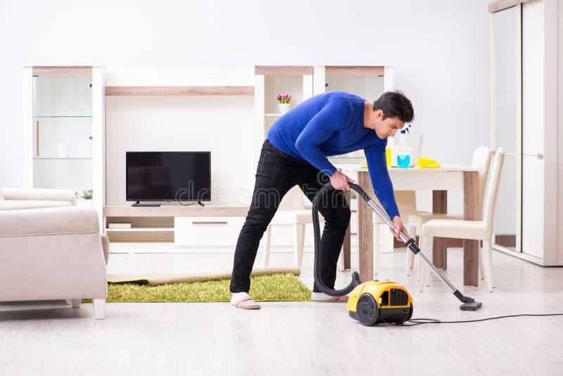 Młody człowiek próżnia czyści jego mieszkanie zdjęcia stock