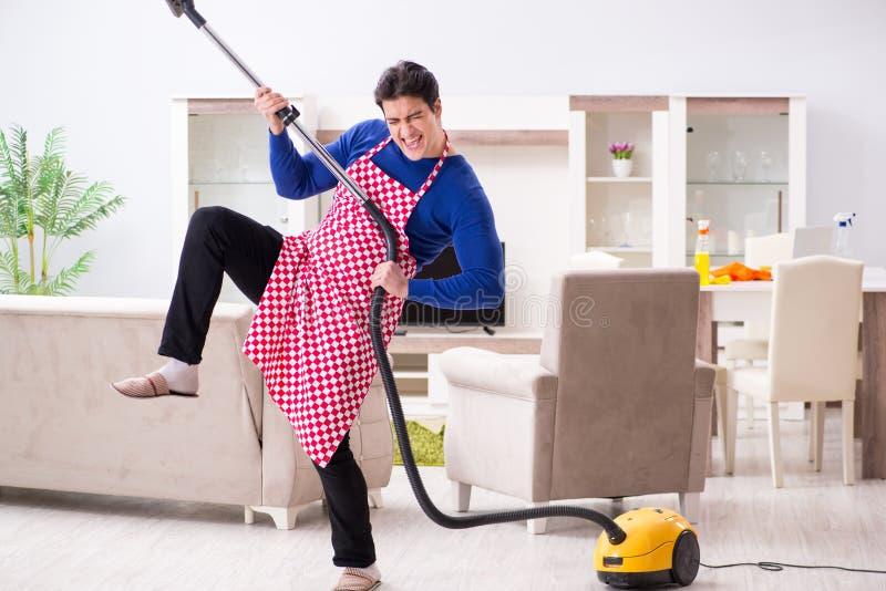Młody człowiek próżnia czyści jego mieszkanie zdjęcia royalty free