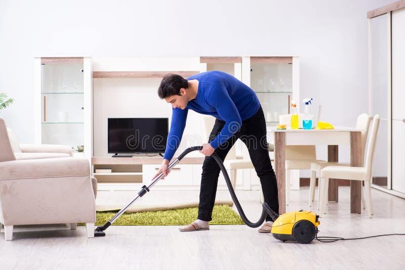 Młody człowiek próżnia czyści jego mieszkanie obraz royalty free