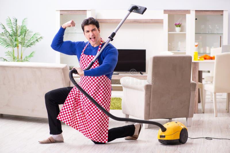 Młody człowiek próżnia czyści jego mieszkanie obrazy stock