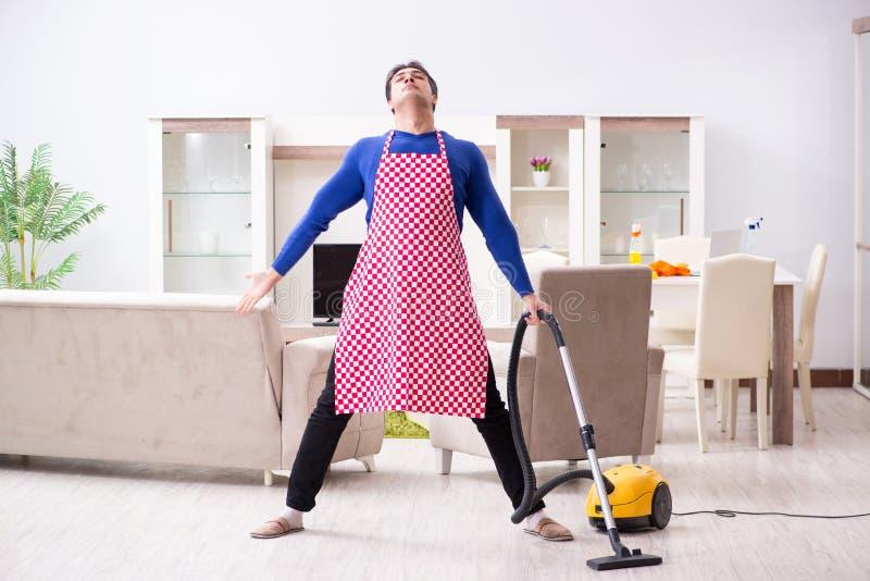 Młody człowiek próżnia czyści jego mieszkanie fotografia royalty free