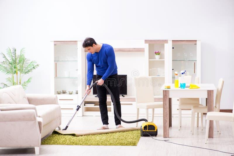 Młody człowiek próżnia czyści jego mieszkanie obraz stock