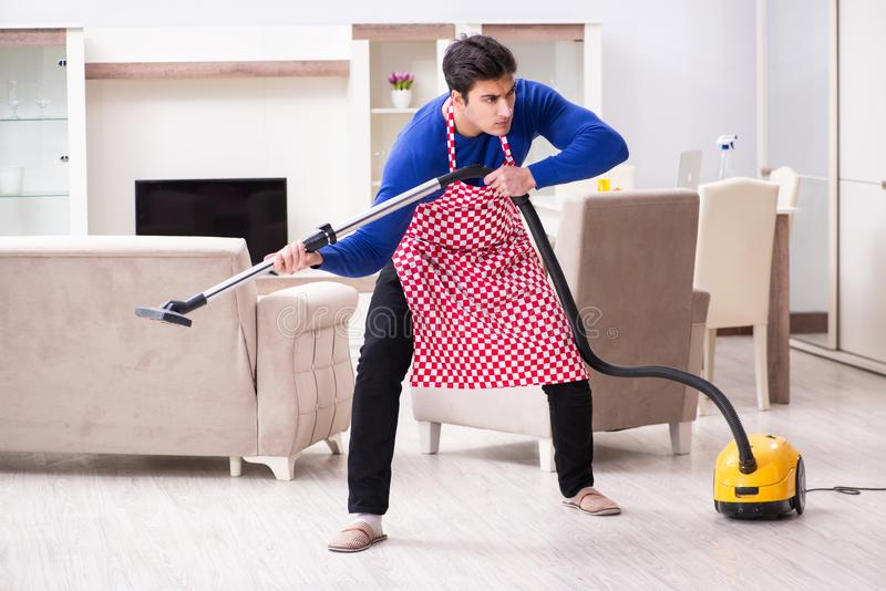 Młody człowiek próżnia czyści jego mieszkanie zdjęcie royalty free