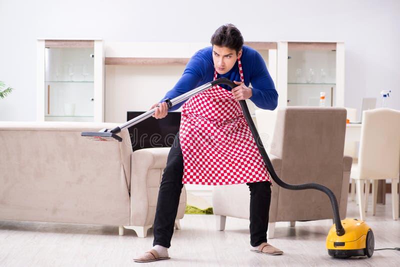 Młody człowiek próżnia czyści jego mieszkanie fotografia stock