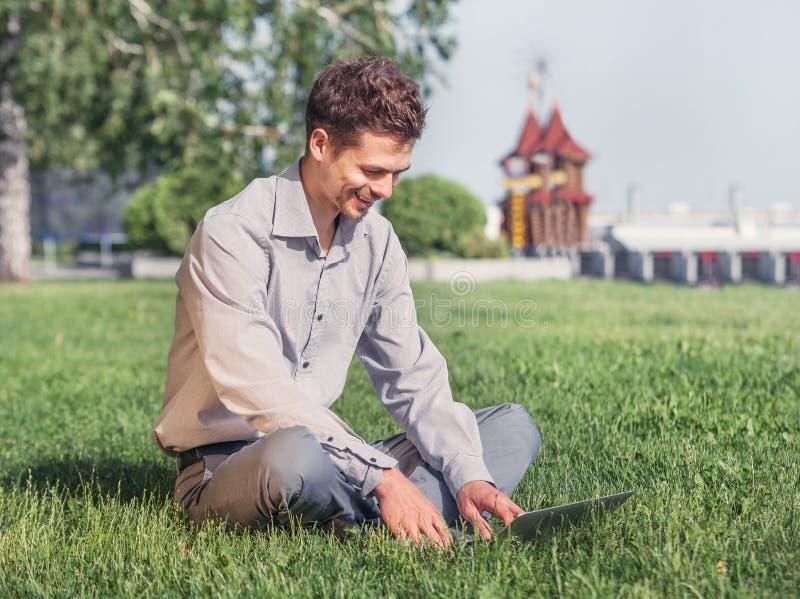 Młody człowiek praca z laptopem w miasto parku fotografia stock