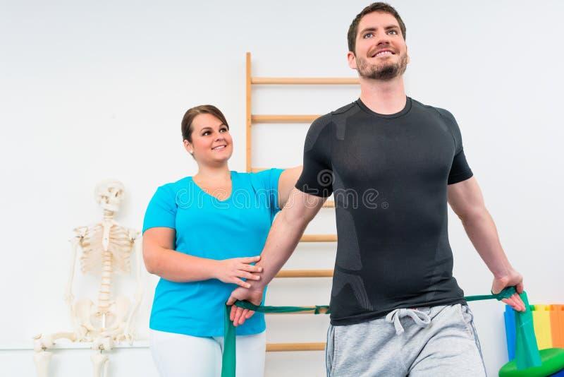 Młody człowiek pracujący z physiotherapist i oporu zespołem out obrazy royalty free