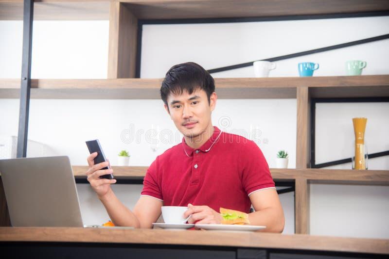 Młody człowiek pracuje na labtop lub komputerze w kuchennym pokoju, loft styl obrazy stock