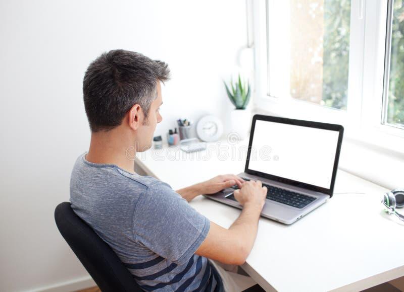 Młody człowiek pracuje na laptopie zdjęcia stock