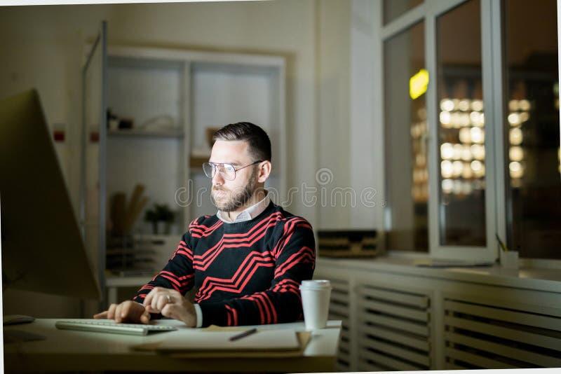 Młody człowiek pracuje póżno w biurze zdjęcia royalty free