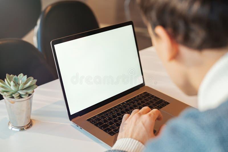 Młody człowiek pracuje przed laptopem z pustym bielu ekranem obraz royalty free