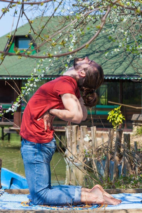 Młody człowiek praktyki joga letni dzień jeziornego rozciągania bocznym widokiem folował ciało strzał zdjęcie stock