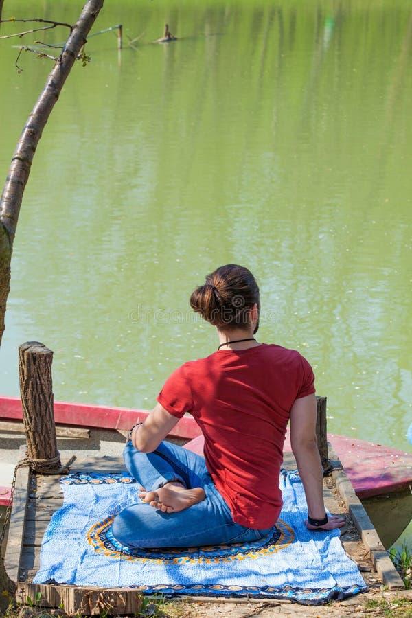 Młody człowiek praktyki joga letni dzień jeziornym pozycji skręcaniem kręgosłup folował ciało strzał zdjęcie stock