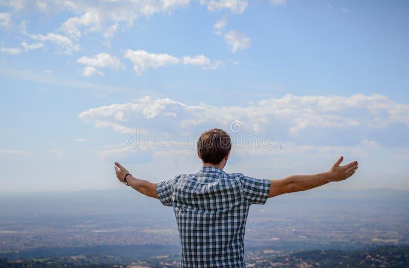 Młody człowiek przegapia krajobraz od wzgórza z jego ręką obraz royalty free