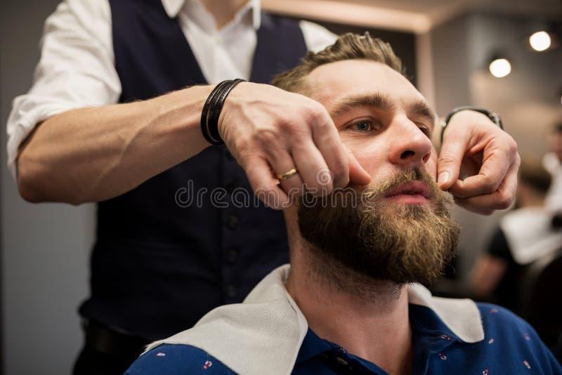 Młody człowiek przy fryzjera męskiego sklepem przygotowywa dla golić zdjęcia royalty free