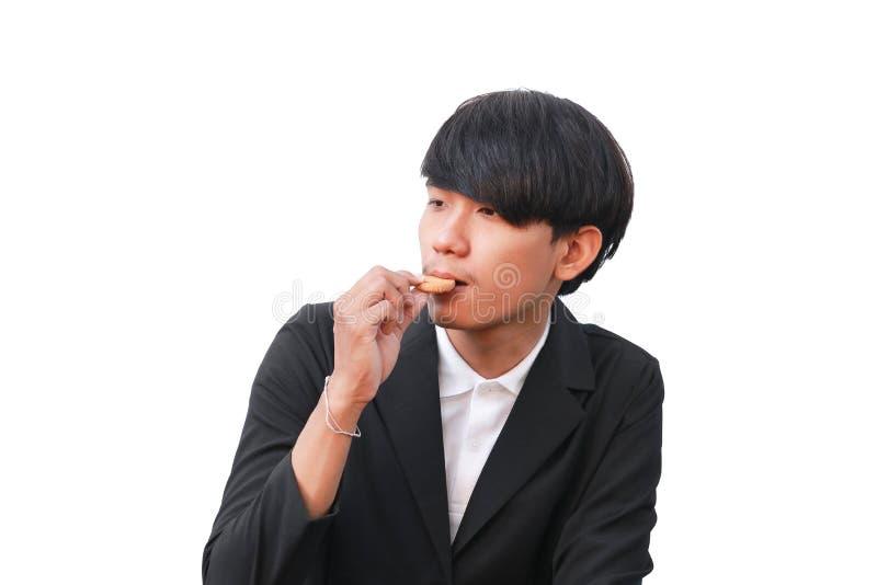 Młody człowiek przystojny je ciastko mali kawałki na białym tle zdjęcie stock