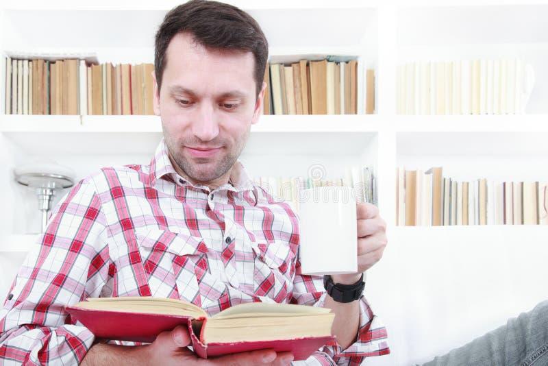 Młody człowiek relaksuje na leżanki czytelniczej książce i cieszy się kawę fotografia royalty free