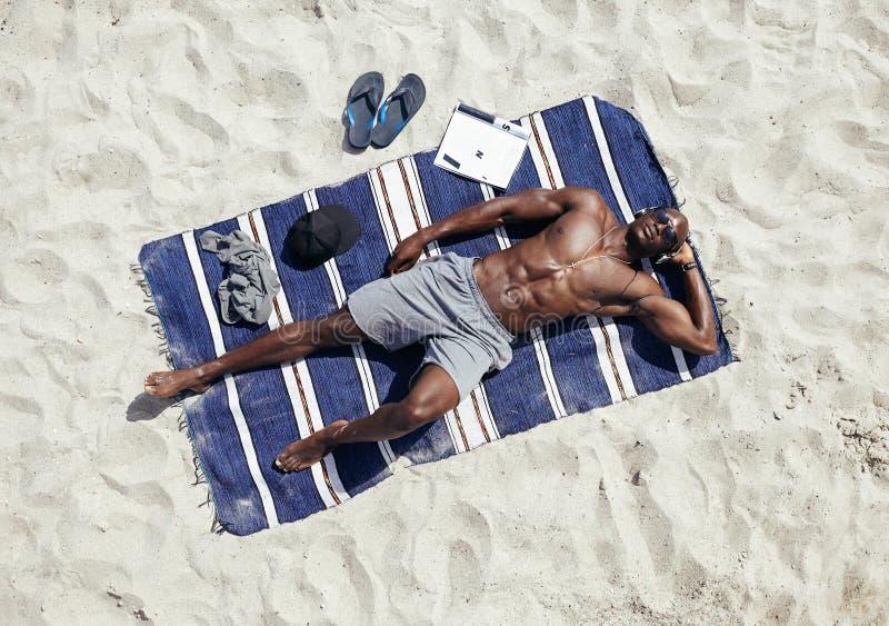 Młody człowiek relaksuje na macie przy plażą obraz royalty free