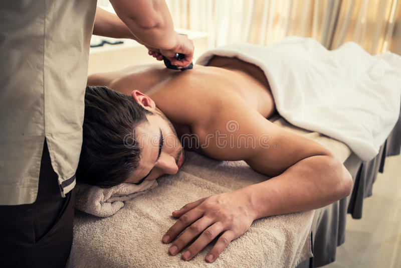 Młody człowiek relaksuje podczas tradycyjnego masażu z gorącymi kamieniami obrazy royalty free
