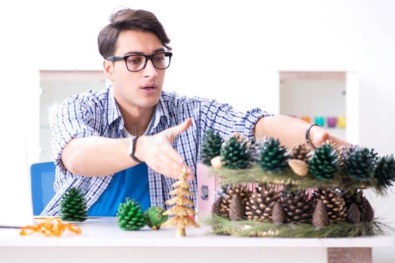 Młody człowiek robi boże narodzenie dekoraci od rożków zdjęcie stock