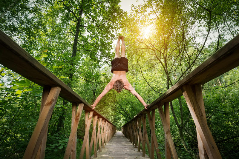 Młody człowiek robi handstand na footbride w lesie obrazy royalty free