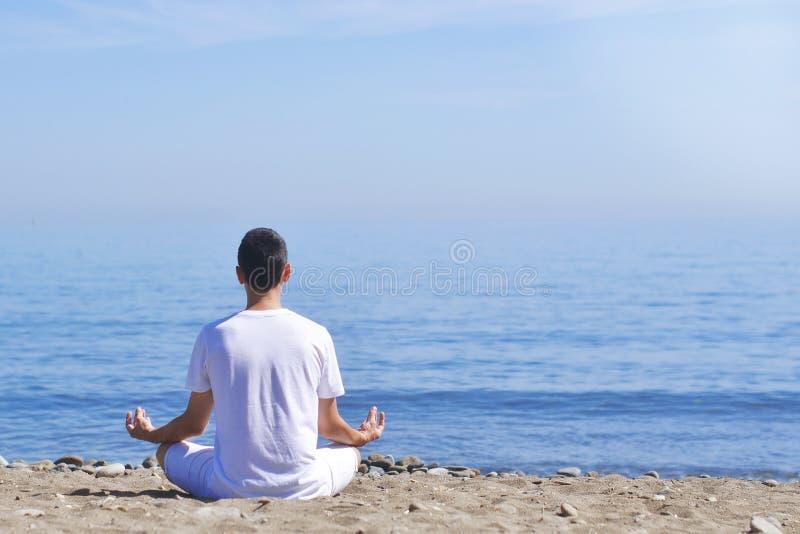 Młody człowiek robi medytaci w lotos pozie na morzu, plaży, harmonii i kontemplaci/oceanu, Chłopiec ćwiczy joga przy dennym kuror zdjęcia royalty free