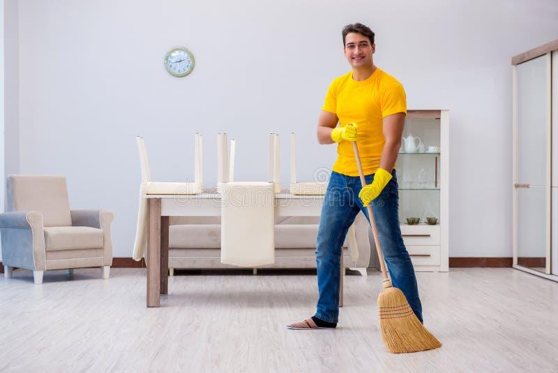 Młody człowiek robi obowiązek domowy w domu zdjęcie royalty free