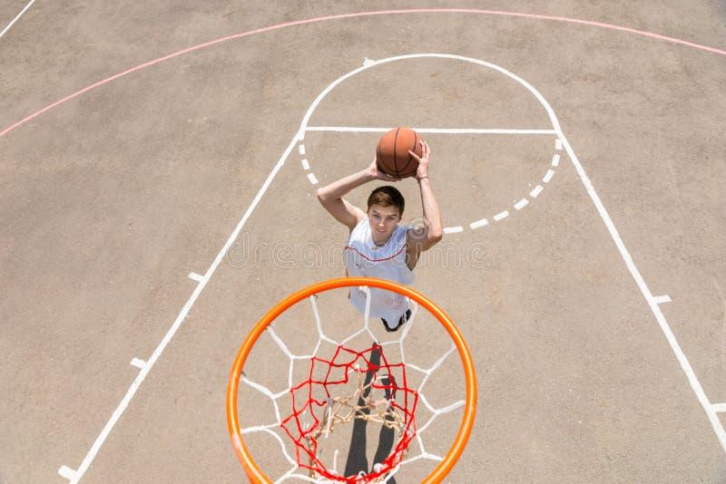 Młody Człowiek Robi rzut z wyskoku na boisko do koszykówki obraz stock
