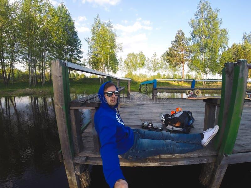 Młody człowiek robi selfie obsiadaniu na molu jeziorem zdjęcie royalty free