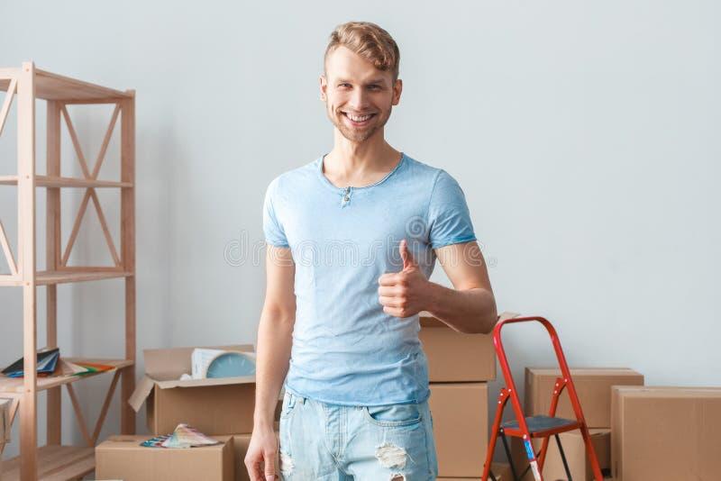 Młody człowiek rusza się nowa miejsce pozycja pokazuje kciuk w górę uśmiechniętego pozytywu fotografia stock