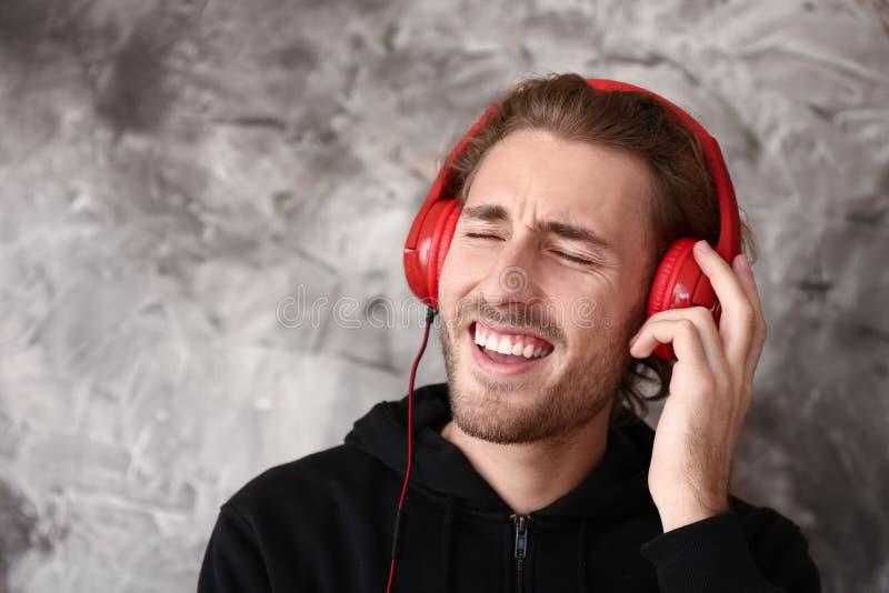Młody człowiek słucha muzyka na grunge tle fotografia stock