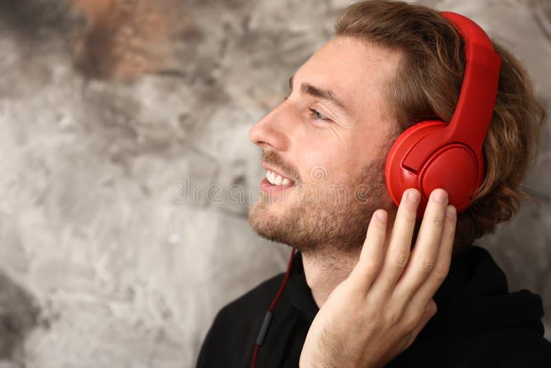 Młody człowiek słucha muzyka na grunge tle zdjęcie royalty free
