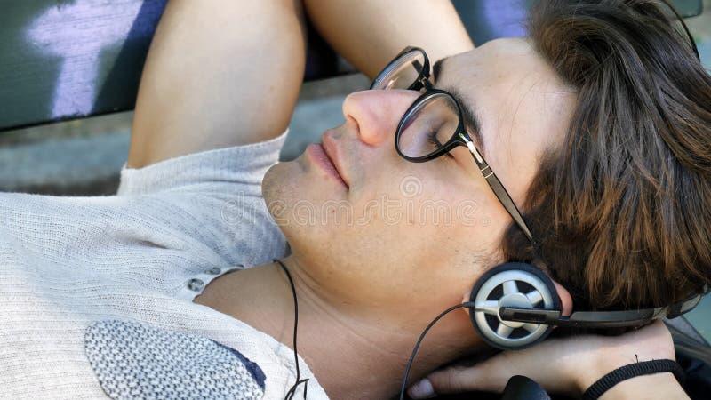 Młody człowiek słucha muzyka w parku zdjęcia royalty free