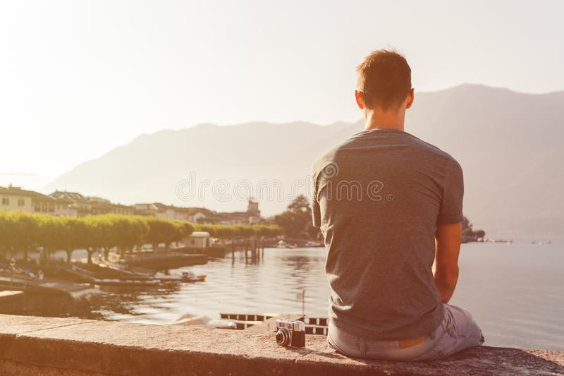 Młody człowiek sadzający na ścianie z rocznik kamerą przed jeziornym deptakiem w Ascona obrazy stock