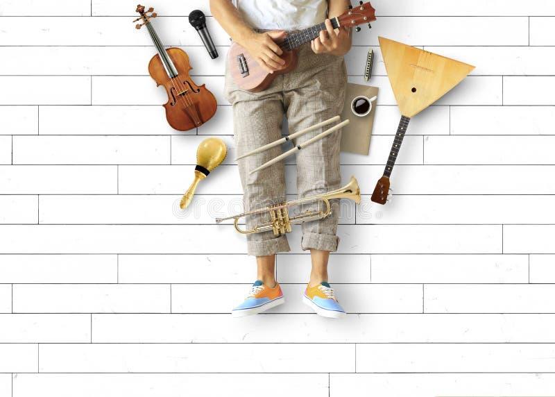Młody człowiek siedzi gitarę i bawić się zdjęcie stock