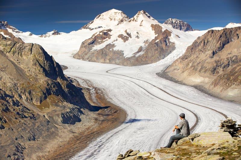 Młody człowiek siedzi majestatycznego widok i cieszy się Aletsch glacie zdjęcie royalty free