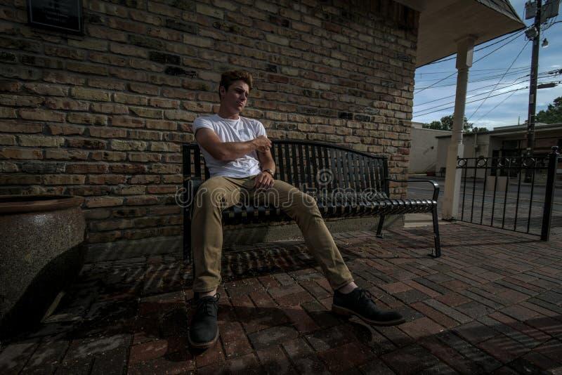 Młody człowiek siedzi na ławce obrazy stock