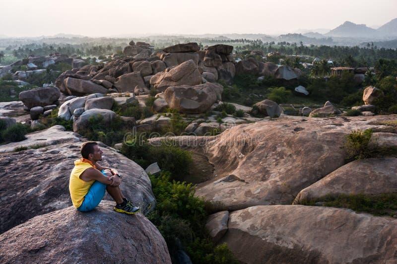 Młody człowiek siedzi na górze z pięknym widokiem i patrzeje naprzód zdjęcie stock