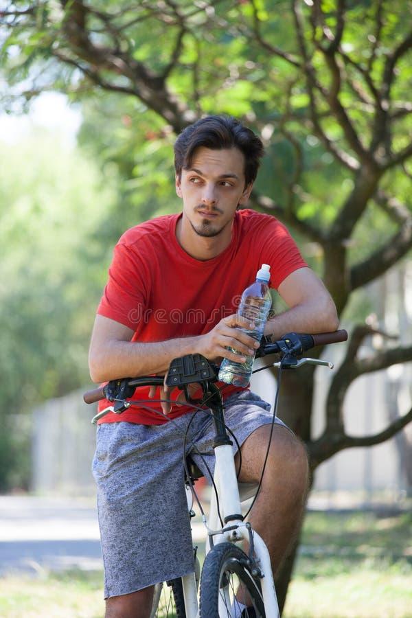Młody człowiek siedzi na rowerze w drewnianej odpoczynkowej chwyt butelce woda fotografia stock