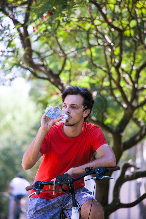 Młody człowiek siedzi na rowerze w drewnianej odpoczynkowej napój wodzie obrazy royalty free