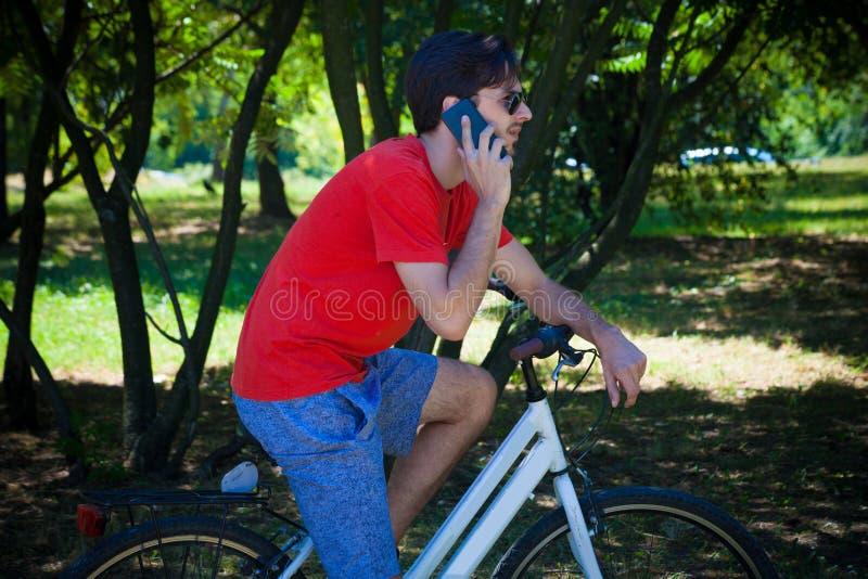 Młody człowiek siedzi na rowerze w drewnianej odpoczynkowej rozmowie na smartphone obraz royalty free